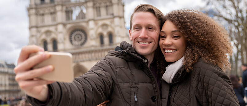 Couple taking a selfie in Paris in front of Notre-Dame